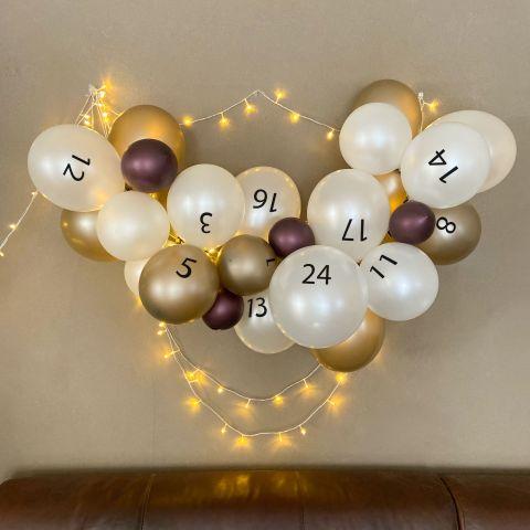 Adventskalender aus Luftballons in den Farben Metallic Weinrot, Metallic Weiß und Metallic Mandel. Die Ballons sind mit den Zahlen 1-24 bedruckt