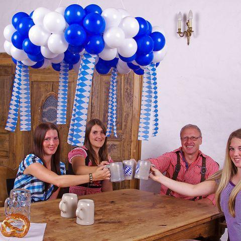 Oktoberfest-Kranz aus blauen und weißen Luftballons, mit Bändern dekoriert hängt über einem Tisch. 4 Personen prosten sich zu.