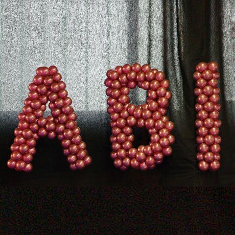 """Große Buchstaben """"ABI"""" aus Luftballons dekoriert auf einem speziellen Gestänge"""