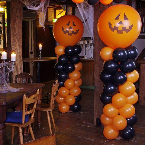 2 Luftballonsäulen in orange und schwarz, mit jeweils einem orangen Riesenballon als Abschluss, mit aufgedrucktem Kürbisgesicht.