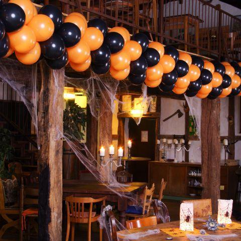 Halloween-Luftballongirlande in schwarz-orange als deko in einem geschmückten Restaurant.