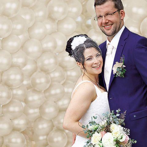 Brautpaar vor Fotohintergrund aufgeblasenen Ballons