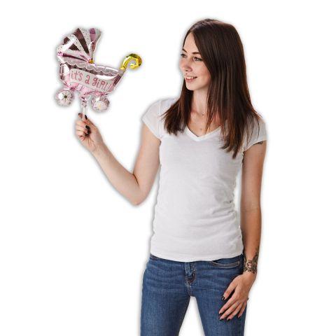 """Folienballon in Form eines rosa Kinderwagens mit der Aufschrift """"It's a girl"""". Eine Person hält den Ballon am Stab in der Hand."""