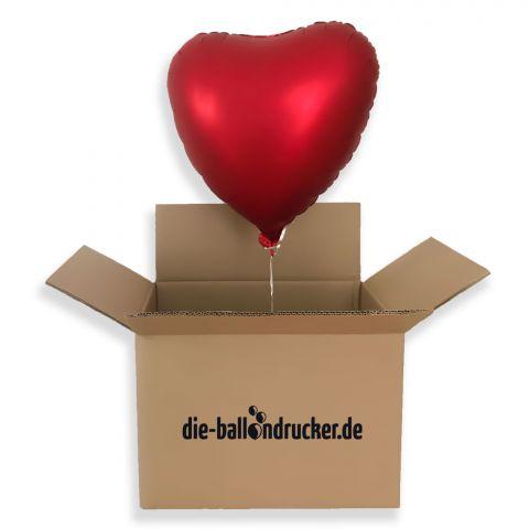 rotes Luftballonherz aus Folie schwebt mit Helium gefüllt als Ballongruß aus einem Karton.