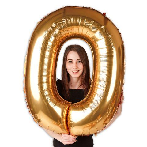 """Großer goldener Folienballon Zahl """"0"""", im Größenverhältnis zu einer Person zu sehen."""