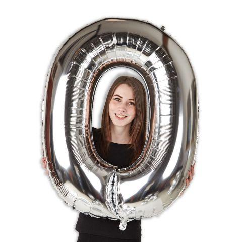"""Großer Folienballon """"0"""" in silber im Größenverhältnis mit Person."""