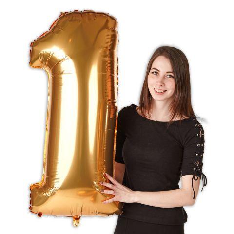 """Großer Folienballon Zahl """"1"""" in gold mit Person zu sehen."""