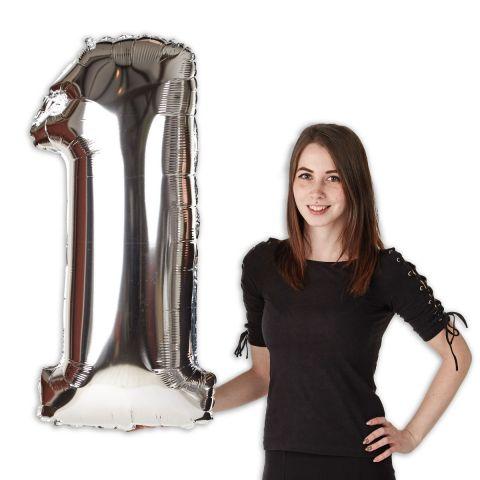 """Folienballon Zahl """"1"""" in Silber, im Größenverhältnis zu Person zu sehen."""