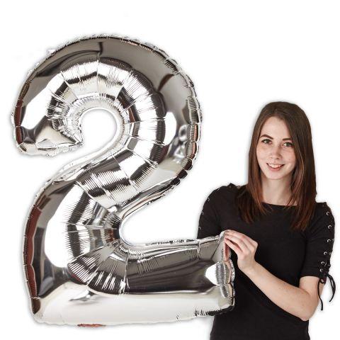 """Folienballon """"2"""" in Silber, im Größenverhältnis zu Person dargestellt."""