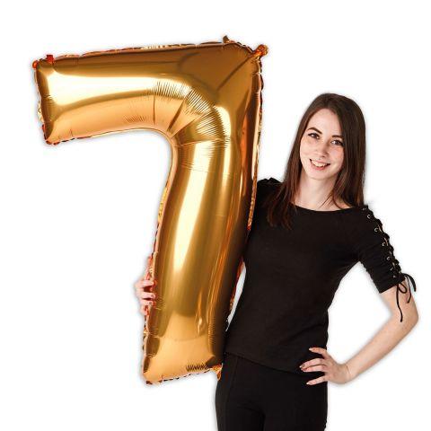 """Goldener Folienballon Zahl """"7"""", groß, neben einer Person zu sehen."""