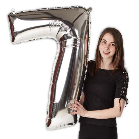 """Folienballon Zahl """"7"""", Silber,  im Größenverhältnis zu einer Person zu sehen."""