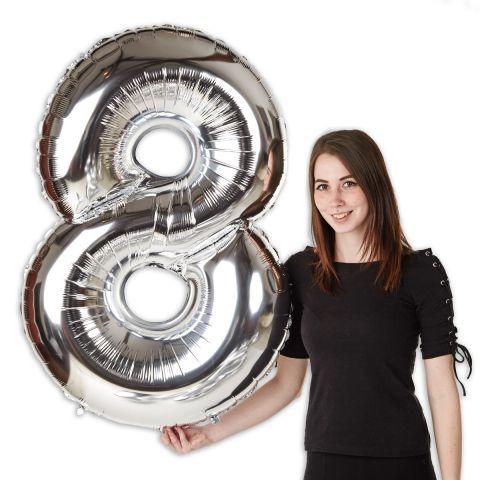 """Folienballon Zahl """"8"""" in silber, im Größenverhältnis zu einer Person zu sehen."""